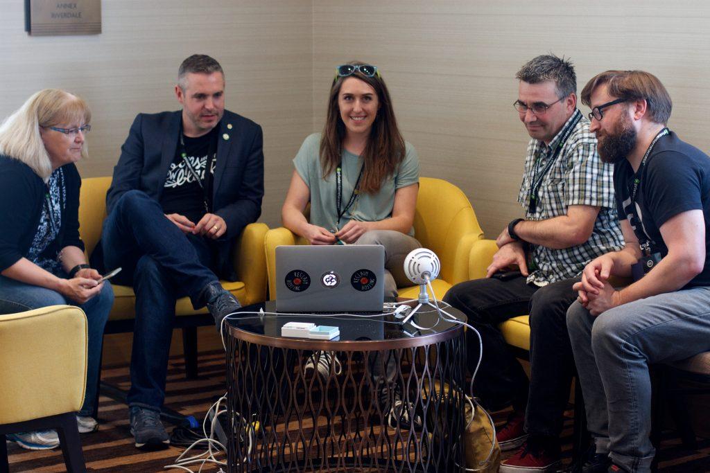 drei Personen vor einem aufgeklapptem Laptop